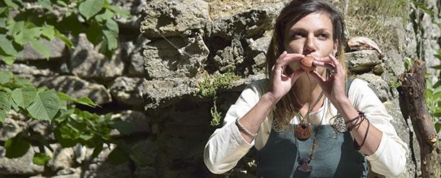 Ung kvinde i vikingetøj spiller på fløjte.