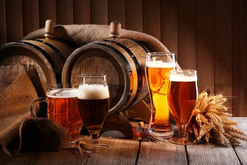 Glas med øl på træbord. Øltønder af træ i baggrunden.