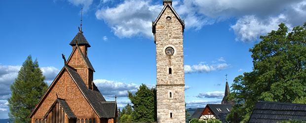 Vikingekirke og tårn med træer og blå himmel i baggrunden.
